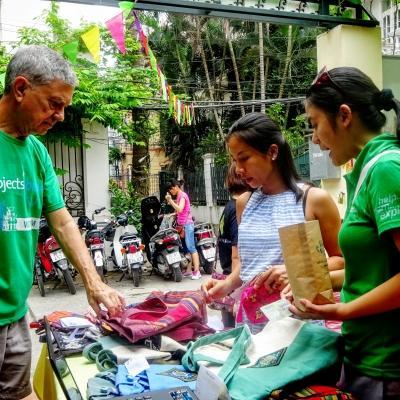 Male and Female International Development Interns sell clothing products at a market during their work placements in Vietnam.